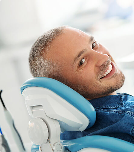 smiling an sitting in a dental chair