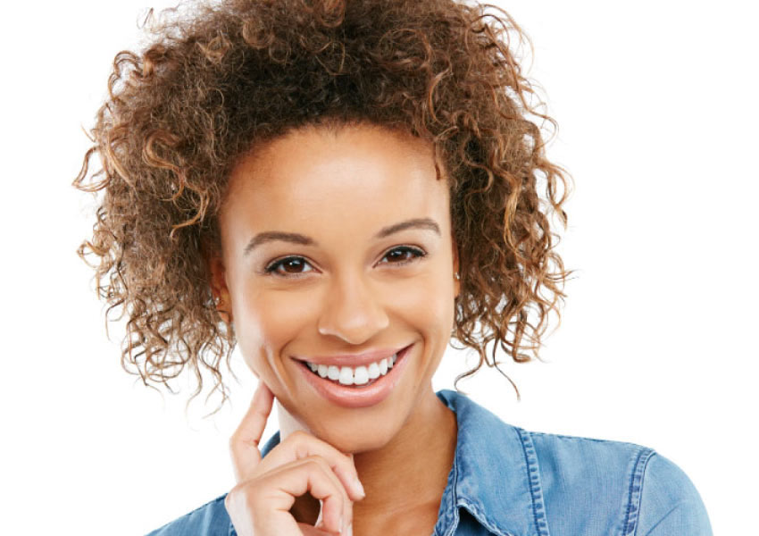 Pretty smiling woman with dark curly hair and beautiful teeth.