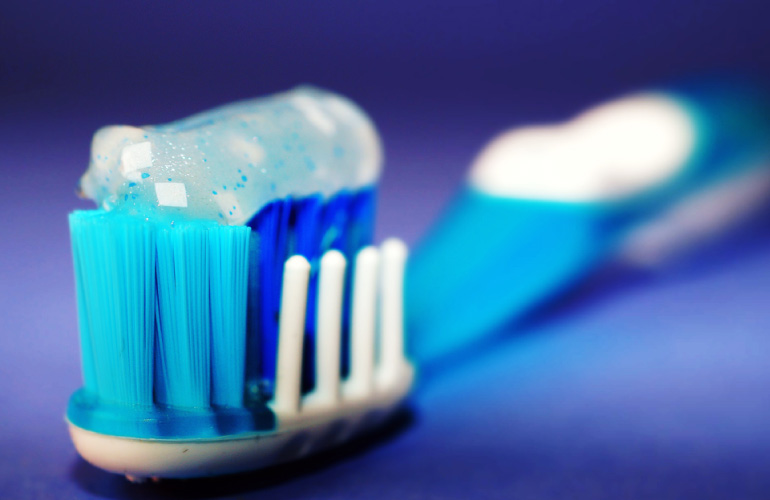 Photo of a blue toothbrush loaded with sparkly toothpaste.