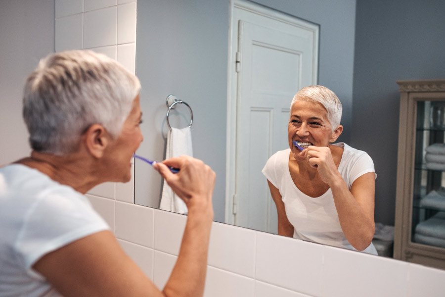 Lady with short gray hair brushing her teeth while looking in the bathroom mirror.