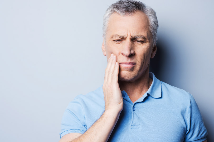 Gray haired man in a blue polo puts his hand to his cheek because of tooth sensitivity.