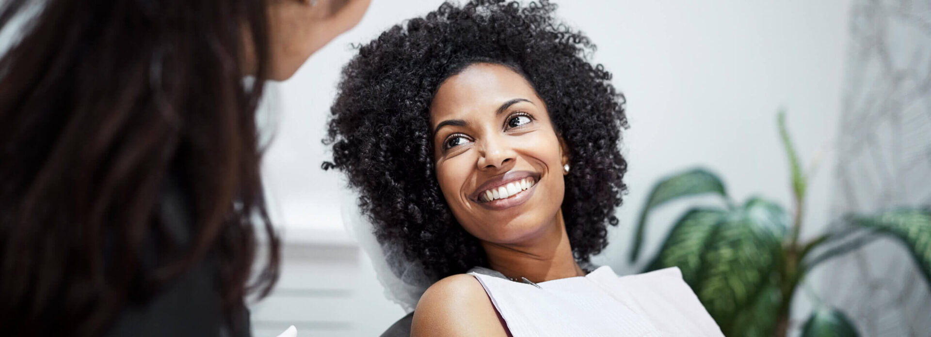 smiling woman speaking with her dentist