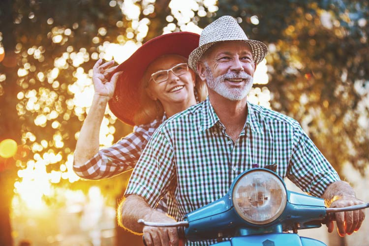 Woman with a big hat rides behind a man on a scooter with the sun filtering through the trees.
