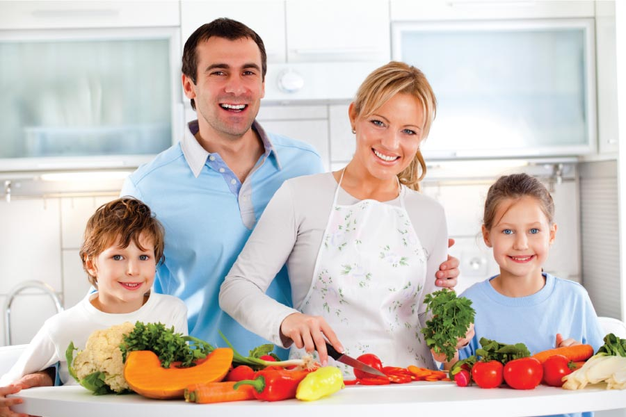 Family of four in the kitchen with healthy food choices before them on the counter.