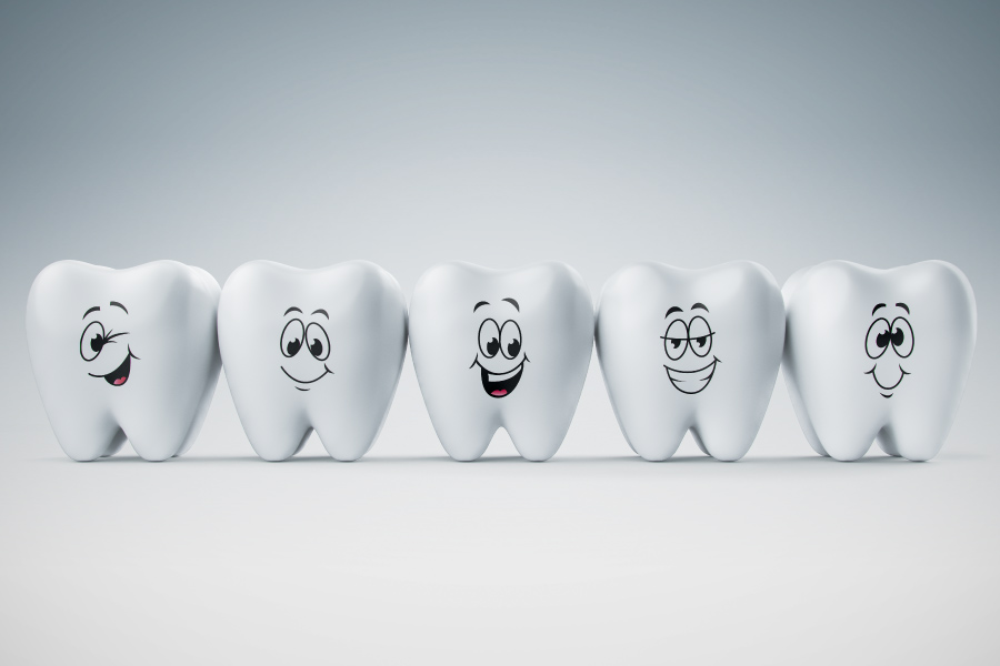 Five tooth models with different cartoonish happy faces.